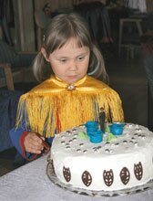 Lapp girl looking at cake
