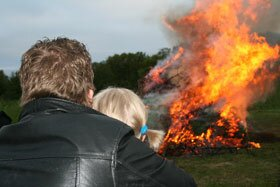 Young Finnish couple watching the Midsummer eve fire in Lapland light